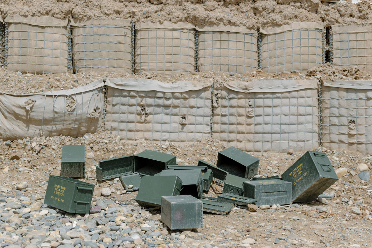 Ammunition cans, emptied during previous battles, lay discarded at an Afghan National Army camp in Helmand Province in April of 2019.