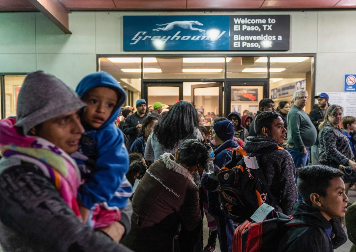 Asylum seekers stand at the Greyhound bus station in downtown El Paso, Texas, late on December 23rd, 2018.