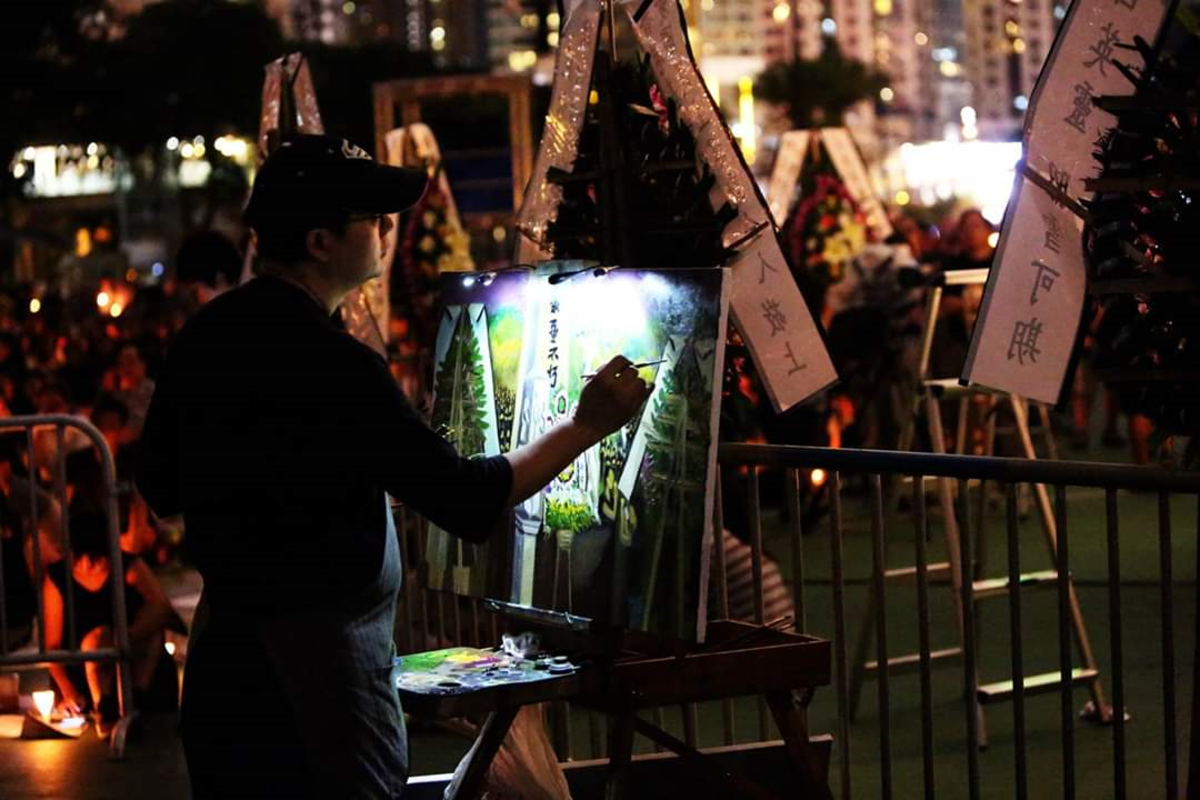 Perry Dino painting in Hong Kong at night.