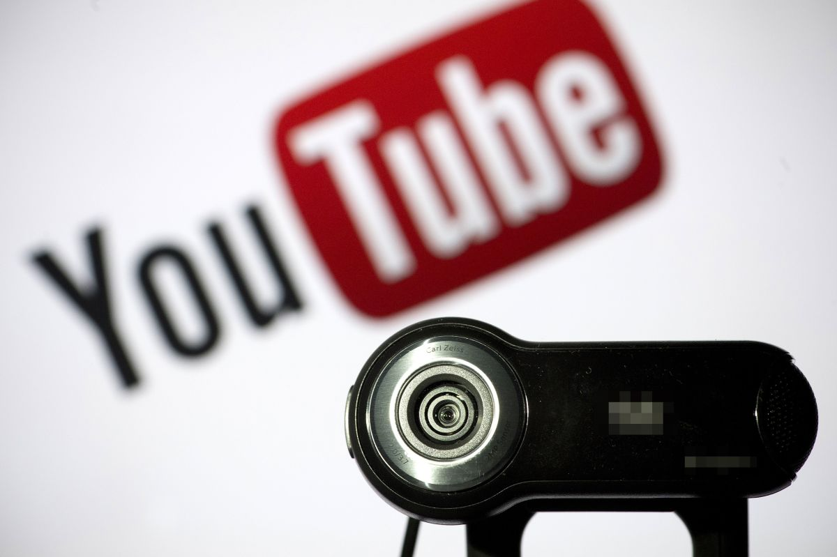 A webcam is pictured in front of the YouTube logo.