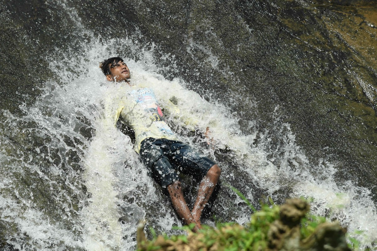 An Indian boy cools off in a waterfall during a hot summer day at the Basistha area in Guwahati, India, on June 13th, 2019. India is experiencing one of the longest and most intense heat waves in decades. Temperatures as high as 123 degrees have been recorded. The heat wave has led to at least 36 deaths since it began last month.