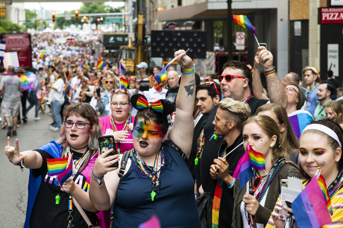 Locals and onlookers shout and wave rainbow flags during the Motor City Pride Parade on June 9th, 2019, in Detroit, Michigan.