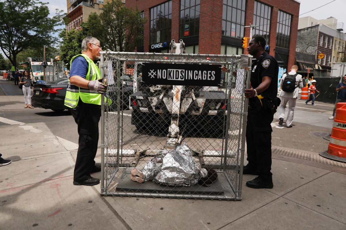 Police take away a pop-up art installation depicting a small child curled up underneath a foil survival blanket in a chain-link cage that stands along a Brooklyn street on June 12th, 2019, in New York City. Representing migrant children in Border Patrol custody, the cages were placed in front of the offices of various news organizations and other highly trafficked areas in Brooklyn and Manhattan.