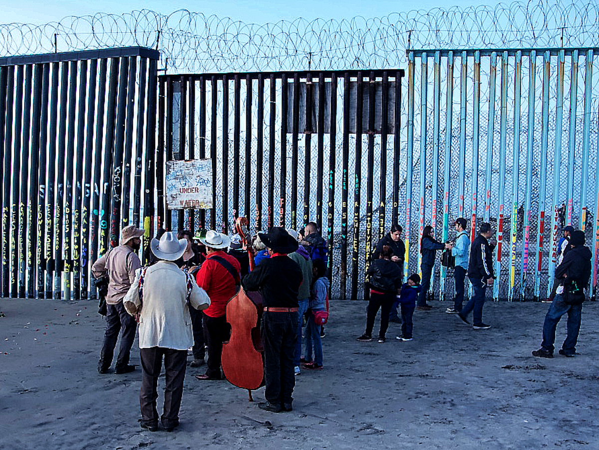 A mariachi band mingles with a crowd on the Mexican side of the wall.