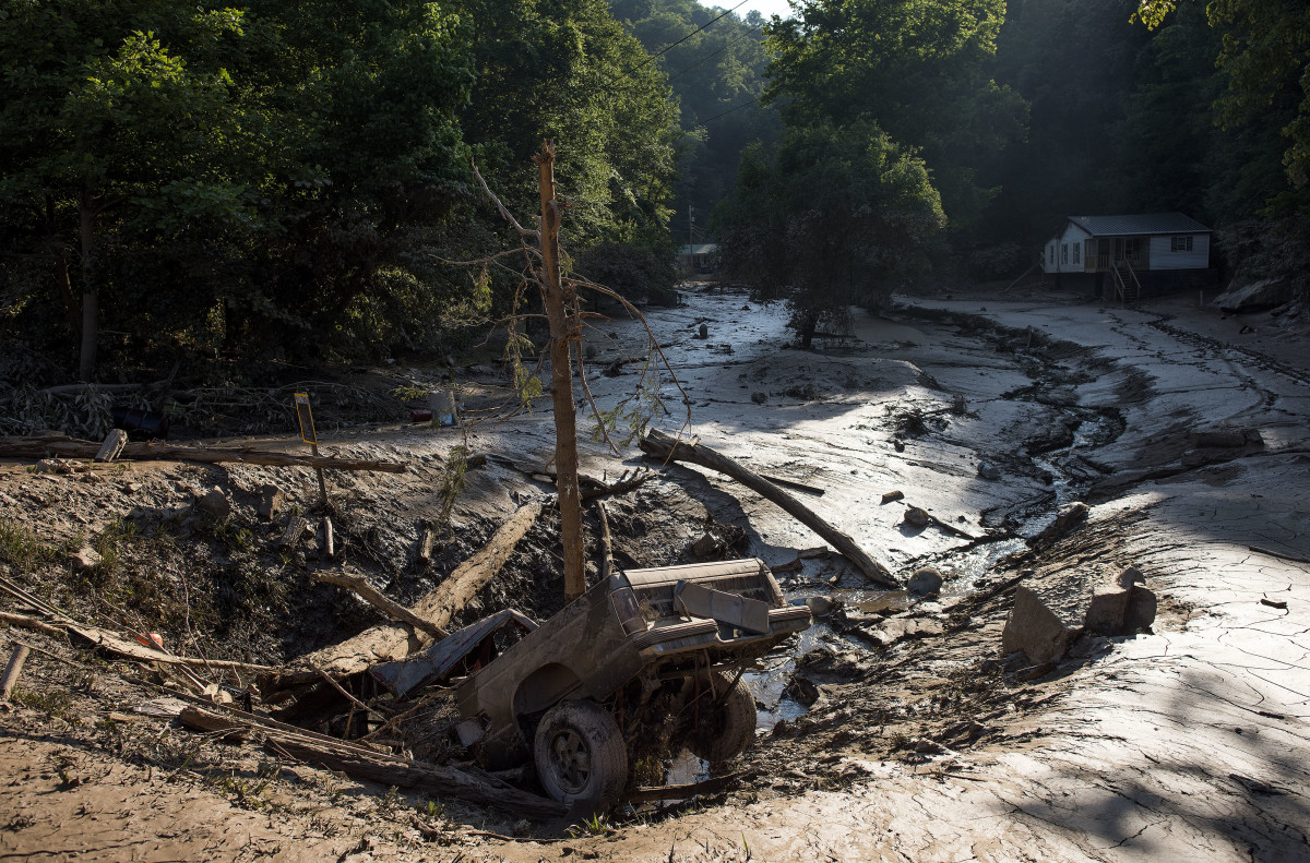 A truck lies in a hole among the mud after it was washed out of the driveway from the flooding on June 25th, 2016, in Clendenin, West Virginia.