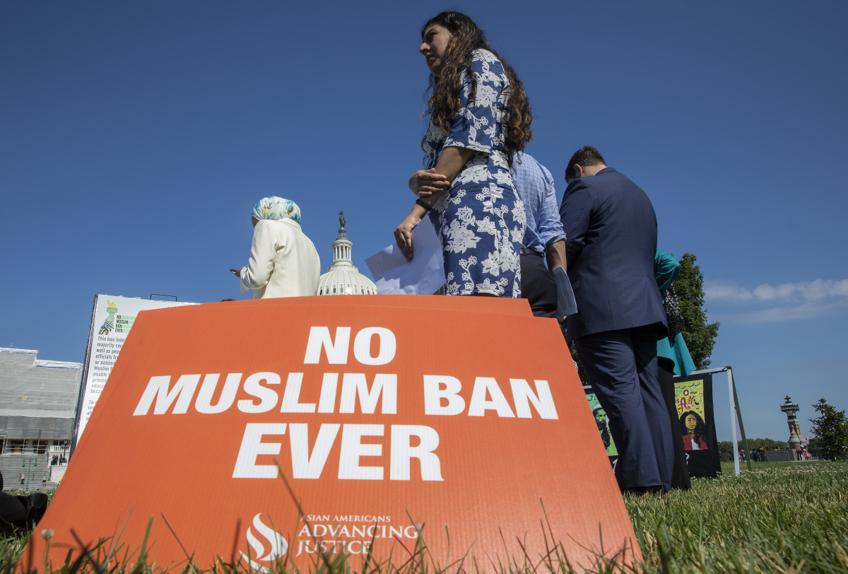 Activists protest on the anniversary of the Supreme Court's ruling upholding the Trump administration's restriction of travel to the U.S. from predominantly Muslim countries.