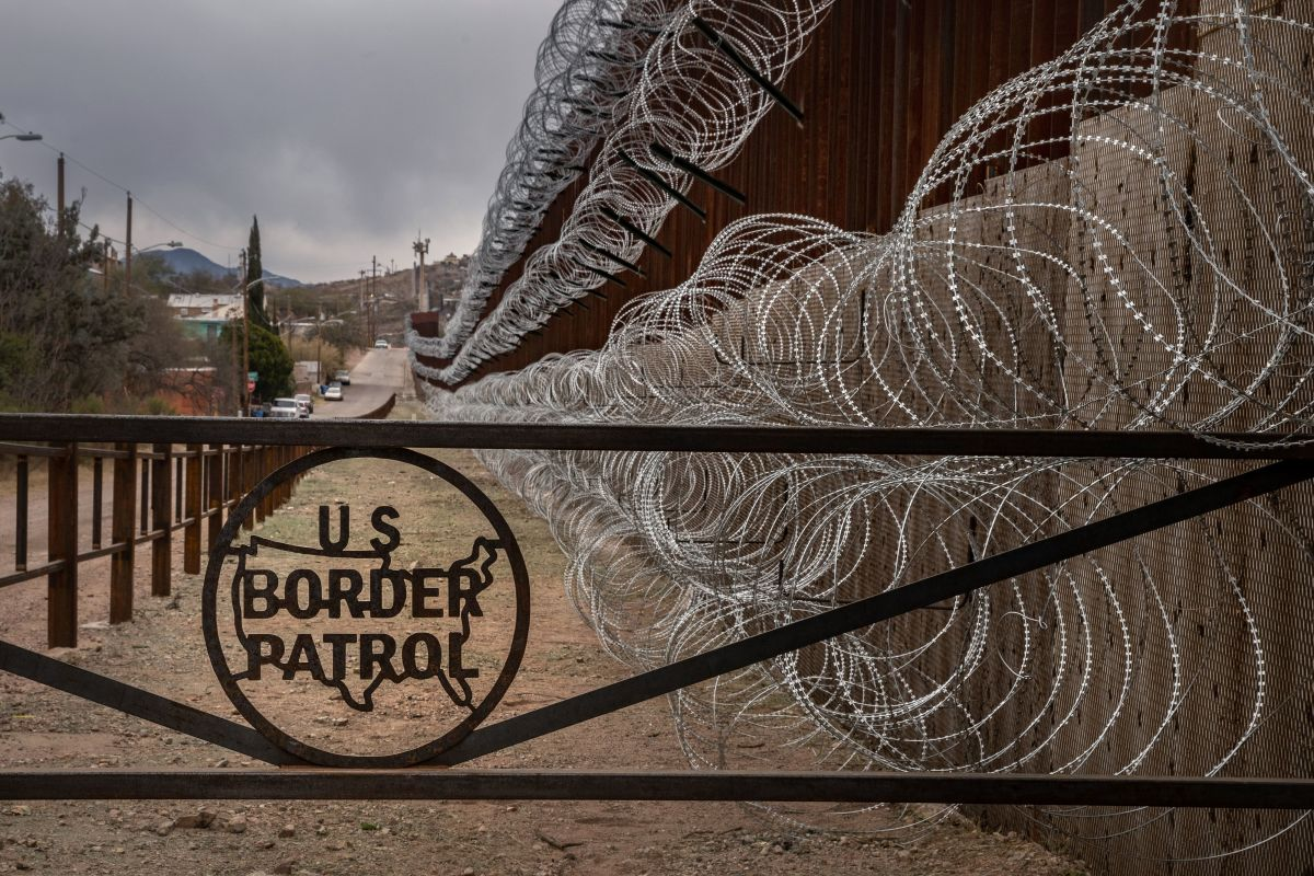 A metal fence marked with the U.S. Border Patrol sign prevents people from getting close to the barbed/concertina wire covering the U.S.–Mexico border fence, in Nogales, Arizona, on February 9th, 2019.
