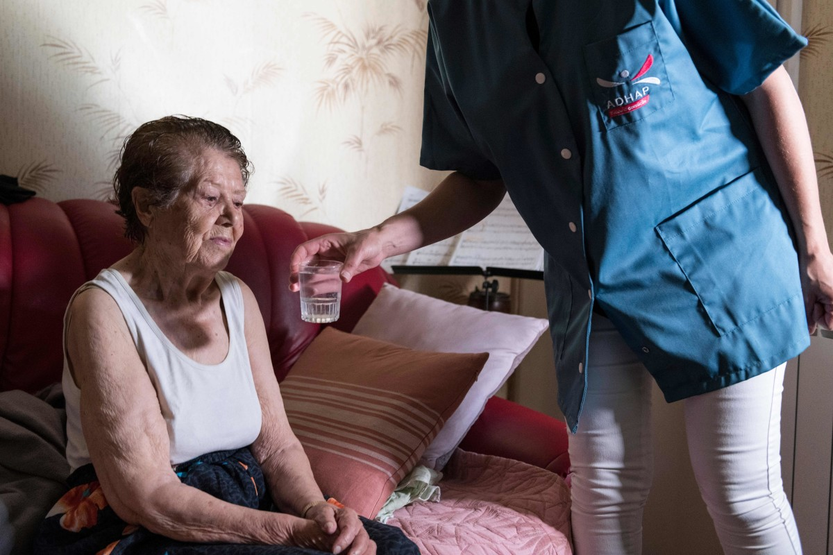 A personal care assistant gives a glass of water to an elderly person as she visits her house to help her to avoid heatstroke and dehydration during the heat wave on June 25th, 2019, in Clermont-Ferrand, France.