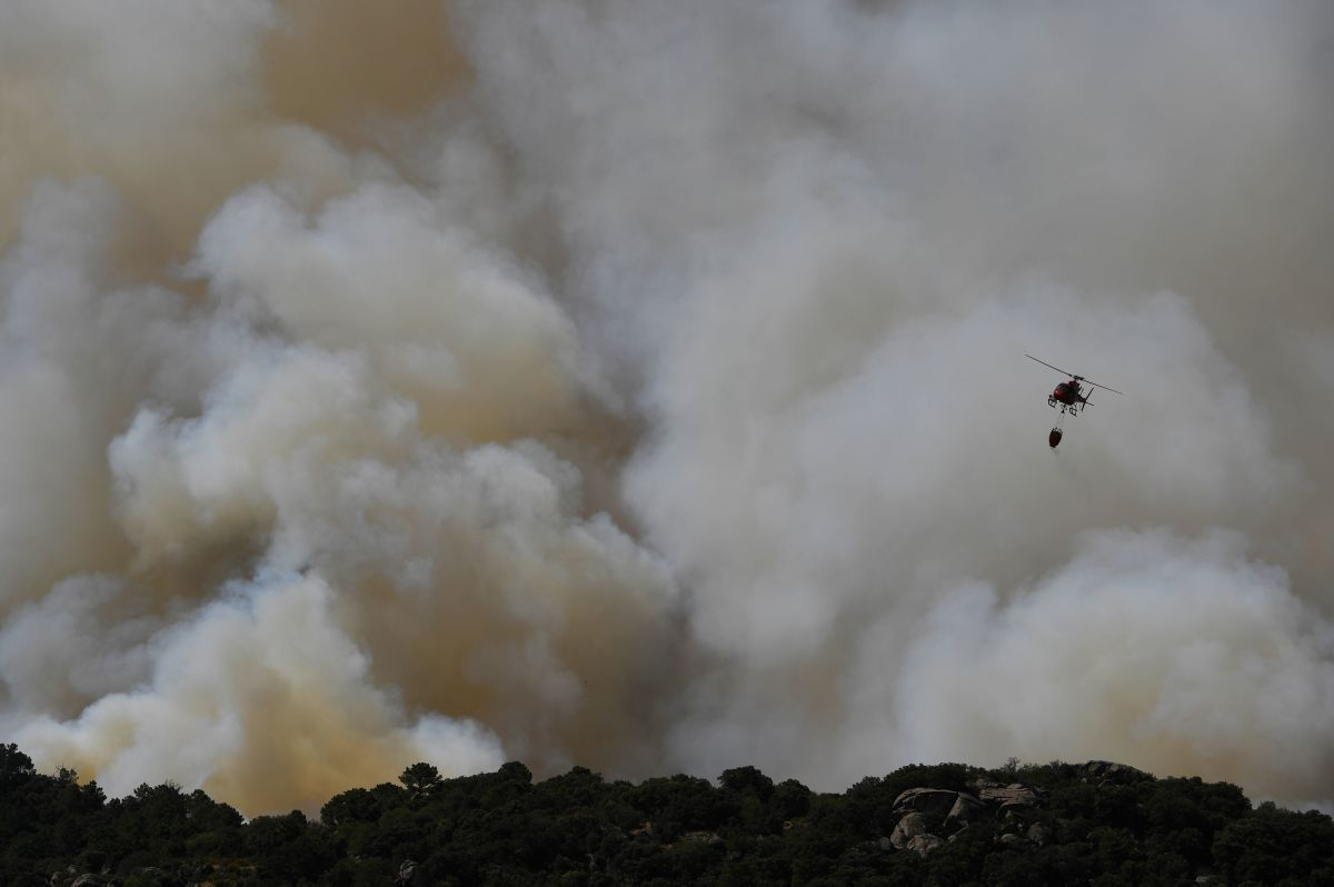 A helicopter drops water over a wildfire in the outskirts of Cenicientos in central Spain on June 29th, 2019. Spain was hit by more wildfires as temperatures remained sky-high in the Europe-wide heat wave, authorities said, just as firefighters finally managed to contain another blaze they had been tackling for nearly 72 hours.