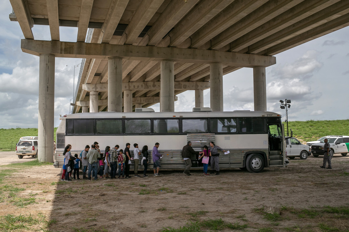 Immigrants wait to be transported to a U.S. Border Patrol processing center after they were taken into custody on July 2nd, 2019, in McAllen, Texas. The immigrants, mostly families from Central America, turned themselves in to border agents after rafting across the Rio Grande from Mexico to seek political asylum in the United States.