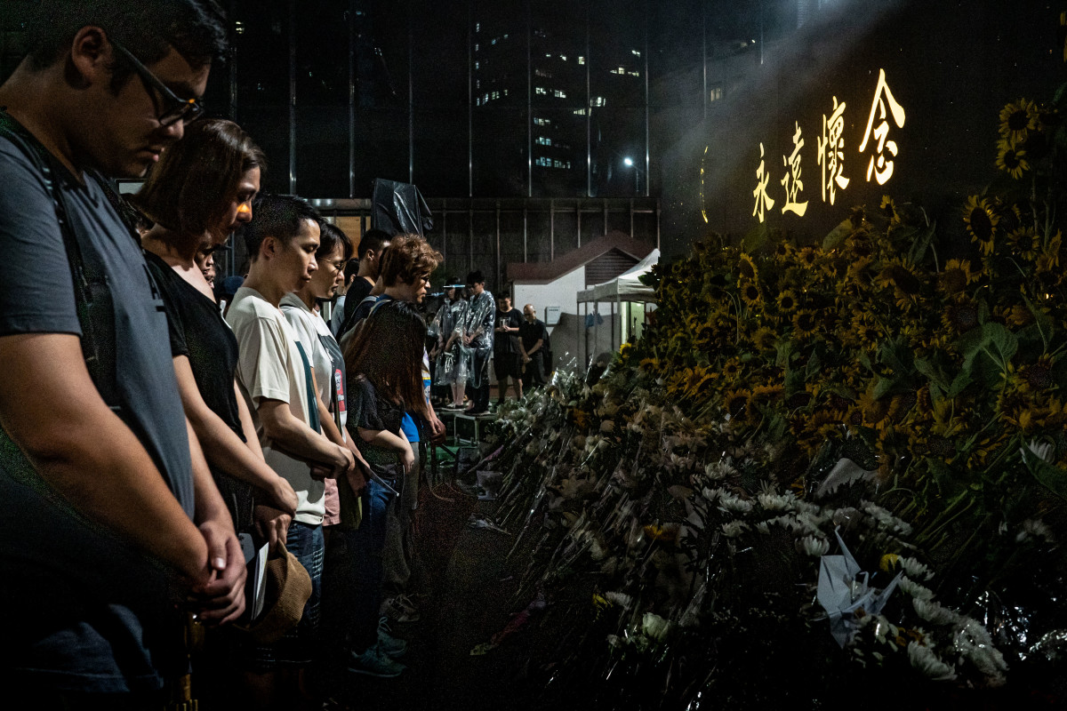 People take a moment of silence during a memorial service for a deceased protester on July 11th, 2019, in Hong Kong.