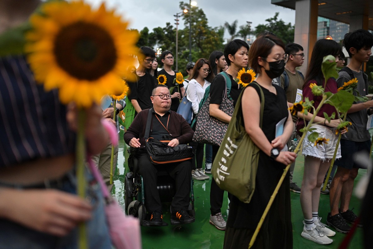 People prepare to pay their respects by placing sunflowers on a stage during a memorial event in Hong Kong on July 11th, 2019, for a young man who plunged to his death while protesting against a controversial extradition bill.