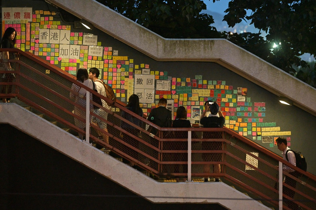 "People write and place handwritten notes onto a makeshift ""Lennon wall"" after attending a memorial event in Hong Kong on July 11th, 2019, for a young man who plunged to his death on June 15th, while protesting against a controversial extradition bill."