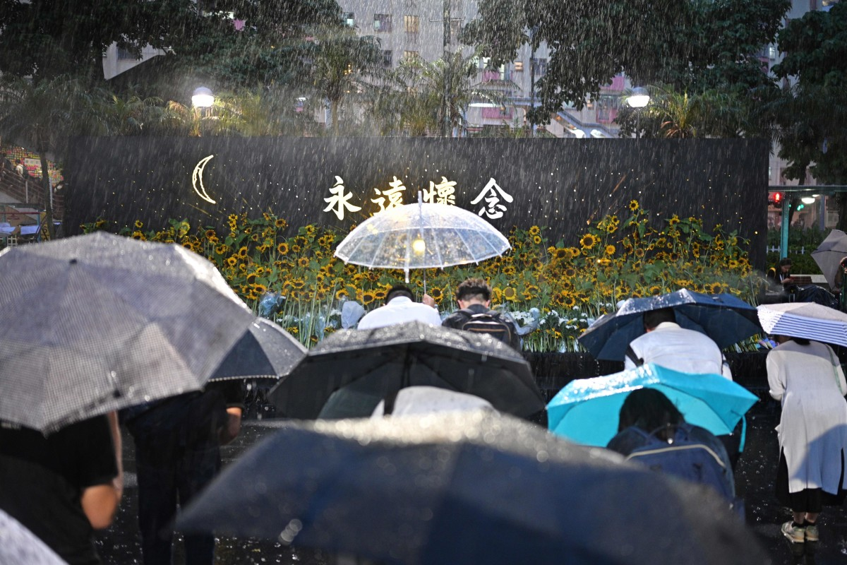 People bow to pay their respects after leaving sunflowers on a stage, as they attend a memorial event during heavy rainfall in Hong Kong on July 11th, 2019.