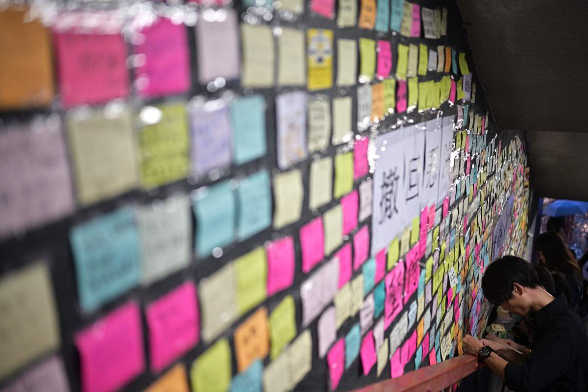 "People write notes before placing them onto a makeshift ""Lennon wall"" on a staircase leading up to a footbridge."