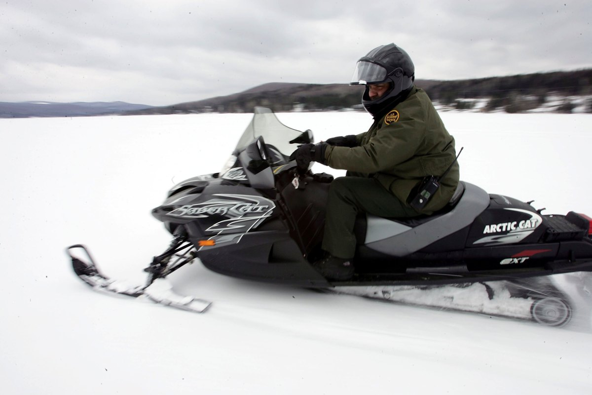 A U.S. Border Patrol Agent rides a snowmobile during a patrol on a frozen lake that splits the Canadian territory behind him and the U.S., near Norton, Vermont.