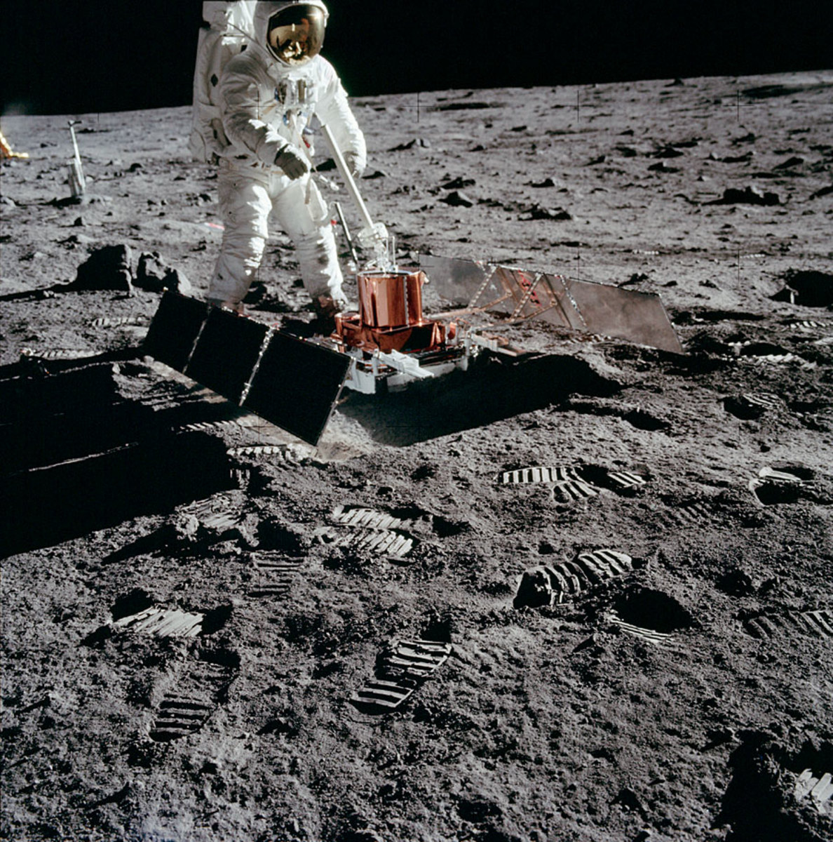 Buzz Aldrin locates a deployment site for the laser reflector and passive seismometer, then sets them up 14 and 19 meters, respectively, south of the Lunar Module.