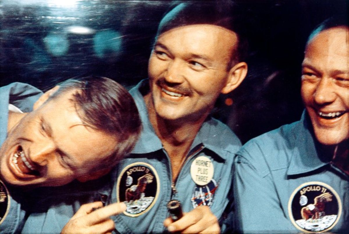 After splashing down safely into the Pacific Ocean, Neil Armstrong, Mike Collins, and Buzz Aldrin smile through the window of the mobile quarantine van.