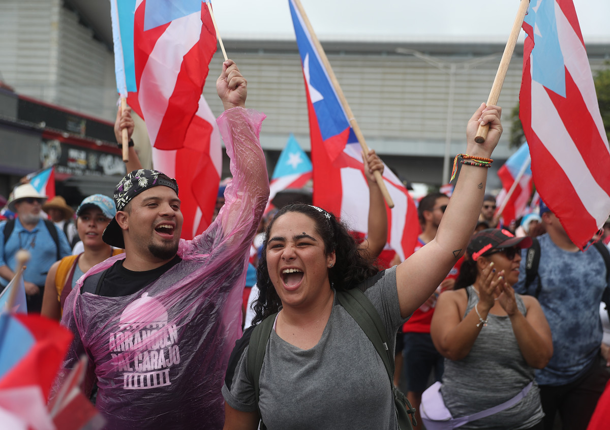 People march through the financial district as they celebrate the ousting of Ricardo Rosselló in Old San Juan, Puerto Rico.