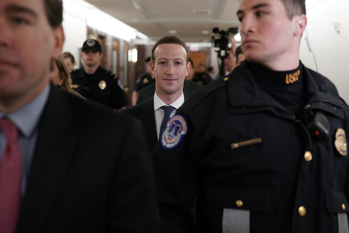 Mark Zuckerberg is escorted through the United States capitol.