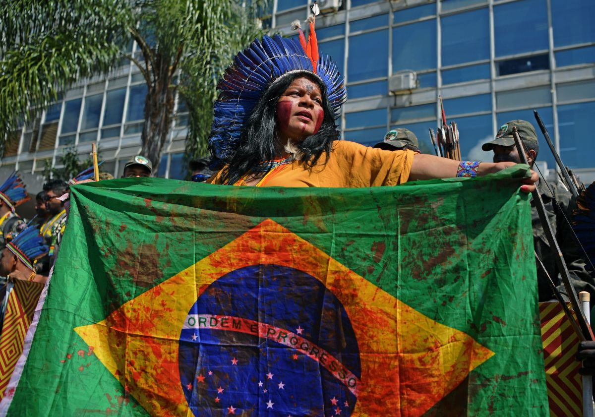 An Indigenous woman holds a Brazilian national flag stained in with a blood-like red during a march in Brasilia on April 26th, 2019, on the last day of a protest to defend Indigenous land and rights.
