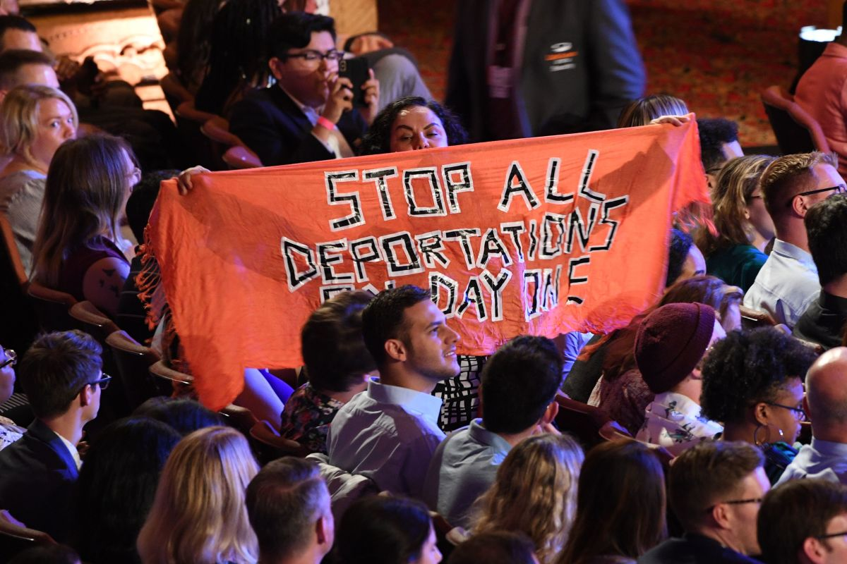 A protester unfurls a banner as Democratic presidential hopefuls participate in the second round of the second Democratic primary debate of the 2020 presidential campaign season hosted by CNN at the Fox Theatre in Detroit, Michigan, on July 31st, 2019.