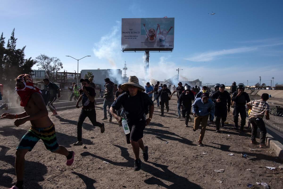 Central American migrants (mostly Hondurans) run along the Tijuana River near the El Chaparral border crossing in Tijuana, Baja California State, Mexico, near the U.S.–Mexico border, after the U.S. border patrol threw tear gas to disperse them after an alleged verbal dispute, on November 25th, 2018.
