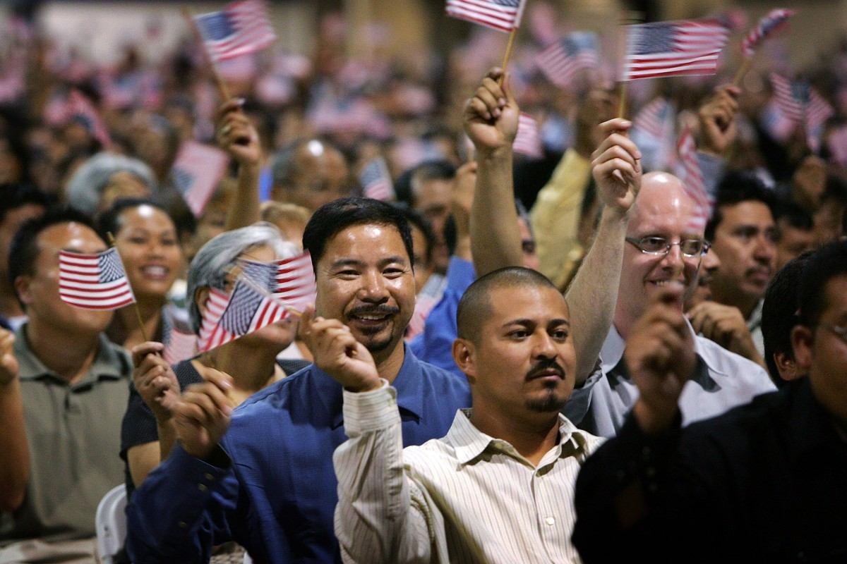 Immigrants wave flags after being sworn in as U.S. citizens in naturalization ceremonies on July 26th, 2007, in Pomona, California.