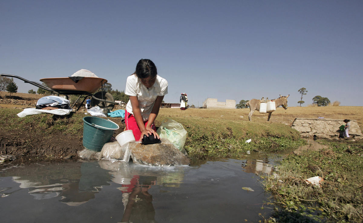 A Mexican Mazahua girl washes some clothes at La Presita reservoir in Loma de Juarez, Mexico.