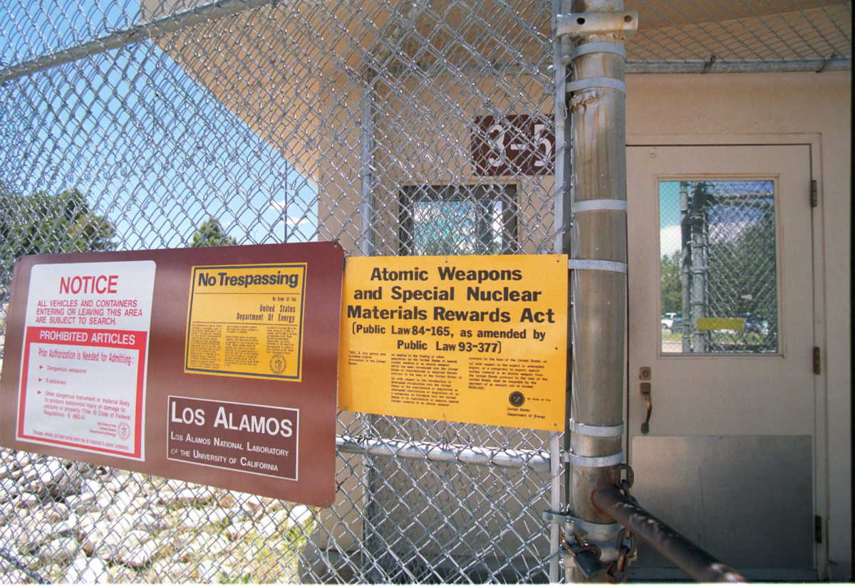 Signs are posted on the gated wall around the main technical area of Los Alamos National Laboratory, New Mexico.
