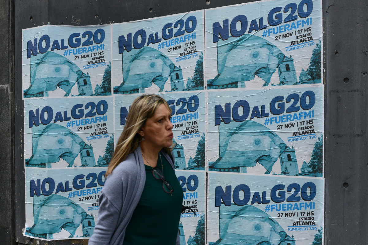 A woman walks past banners against G20 and the International Monetary Fund on the day before the beginning of the G20 Leaders' Summit 2018 on November 29th, 2018, in Buenos Aires, Argentina. Over 24,000 police officers and security agents work on the G20, which gathers the leaders of the top 20 industrialized nations of the world during a two-day meeting on November 30th and December 1st.