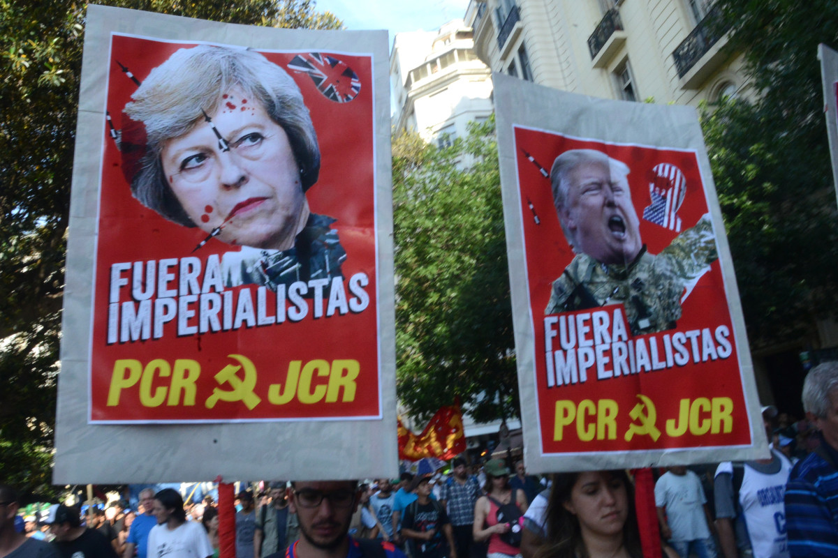 Communist demonstrators hold up posters decrying United Kingdom Prime Minister Theresa May and U.S. President Donald Trump as imperialists in Spanish in Buenos Aires on November 30th, 2018.