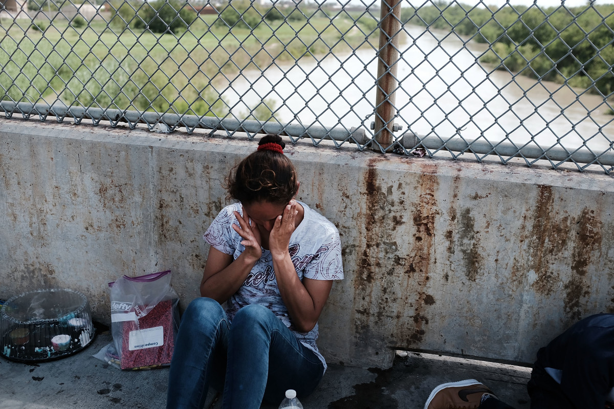 A Honduran woman waits along the border bridge after being denied entry into the U.S. from Mexico on June 25th, 2018, in Brownsville, Texas.
