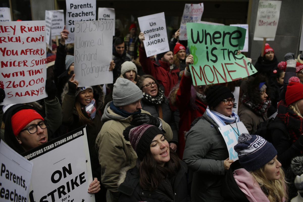 Educators from the Acero charter school network hold signs as they protest during a strike outside Chicago Public Schools headquarters on December 5th, 2018, in Chicago, Illinois. Teachers are asking for smaller class sizes, fair pay, and better resources to continue teaching the more than 7,000 students who attend Acero schools.