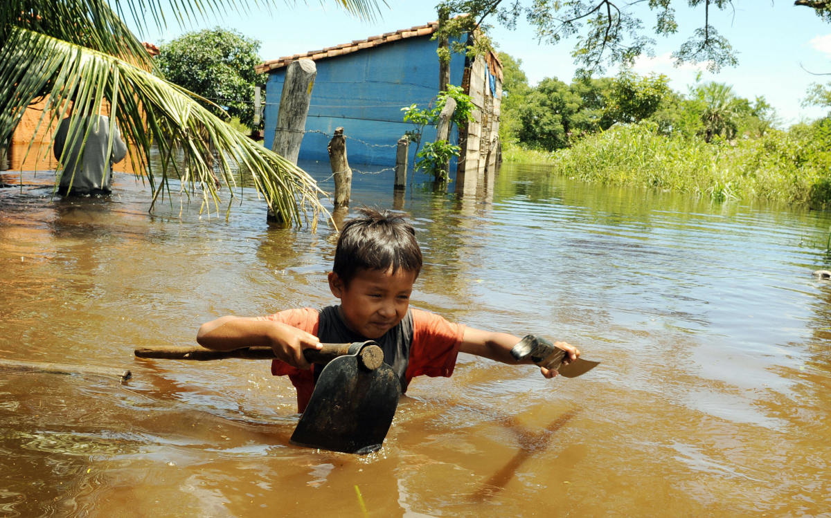 Bolivian boy Pedrito Arce wades through the water carrying some of his family's belongings in the flooded hamlet of Los Bibosi.