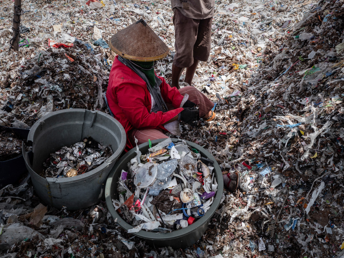 "A woman collecting plastic to recycle at a plastic waste dump in Mojokerto on December 5th, 2018, in Mojokerto, East Java, Indonesia. Indonesia's second-largest city of Surabaya has recently been shortlisted by the Guangzhou Institute for Urban Innovation as one of the most sustainable cities among 900 other cities with its participatory waste management system and involvement of residents in various city projects such as the the ""Suroboyo bus,"" a bus service launched in April that allows passengers to pay for tickets with used plastic bottles. Indonesia, which struggles with grid-locked traffic in its congested cities, is ranked the second-largest plastic polluter in the world behind only China, with reports showing that the country produces 187.2 million metric tons of plastic waste each year. Producing an average of 9,800 cubic meters of waste daily, Surabaya's residents hope to raise public awareness on issues that relate to plastic trash through initiatives like the Suroboyo bus, which is able to collect up to 550 pounds of plastic bottles a day."