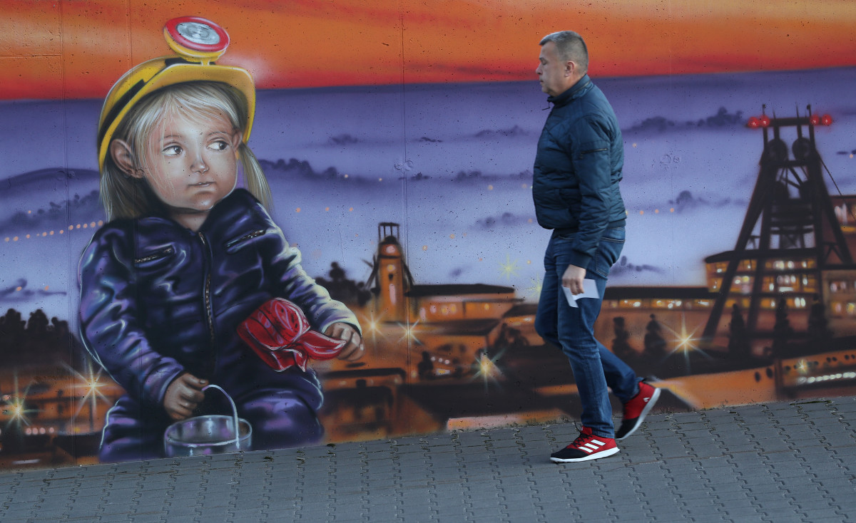 A man walks past a mural outside the corporate headquarters of the JSW mining company on November 30th, 2018, in Jastrzebie Zdroj, Poland. JSW operates mines including the KWK Pniowek mine at nearby Pawlowice, Poland's largest coal mine, with 3,900 miners descending below ground to churn out 13.5 thousand tons of high-grade coal each day that will be destined for coking at steel mills across Europe. The United Nations COP24 climate conference began on Sunday in nearby Katowice.