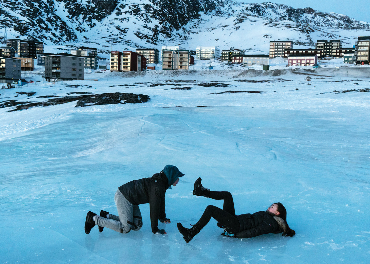 Photo showing two young adults playing on an icy stretch in front of a Greenlandic village (hi res version)
