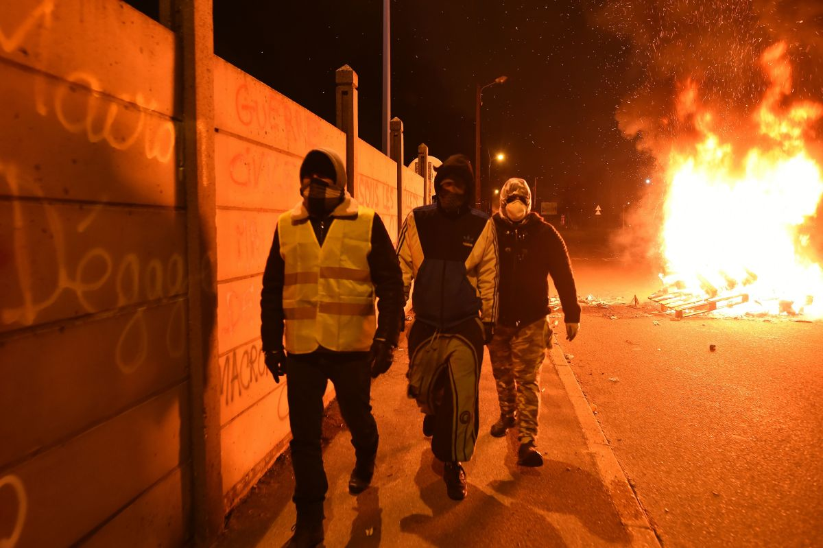 """Yellow vest"" protesters blocking access to an oil depot walk alongside a wall inscribed with ""Macron resign"" as barricades burn in the background on December 11th, 2018, in Le Mans, northwestern France."