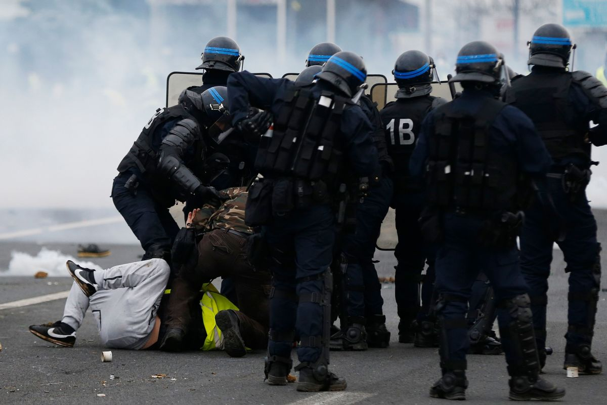"French riot police officers detain protesters during a ""yellow vest"" demonstration in Mondeville, near Caen, France, on December 8th, 2018."