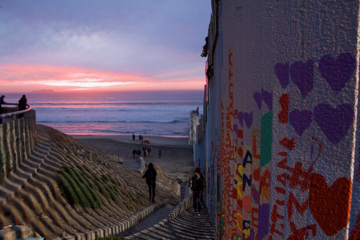 The border wall juts out from the beach 100 yards into the Pacific Ocean.