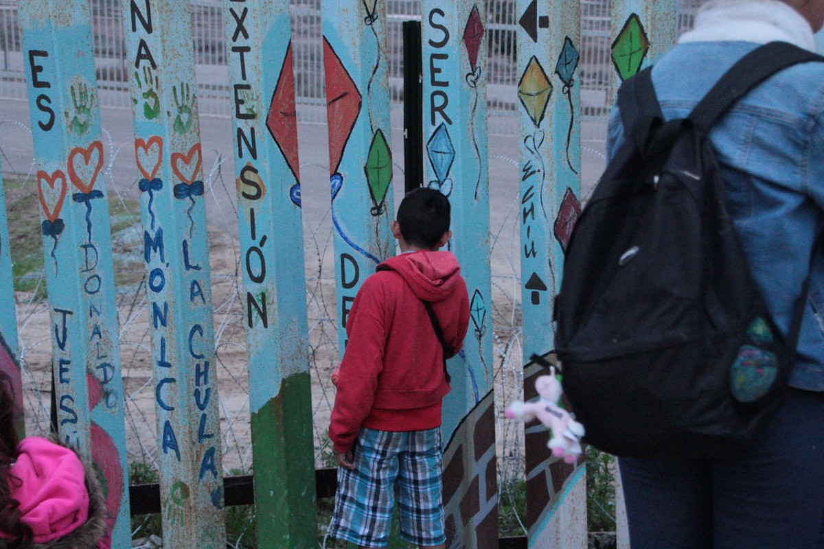 Marisol's 14-year-old son looks through the border wall.