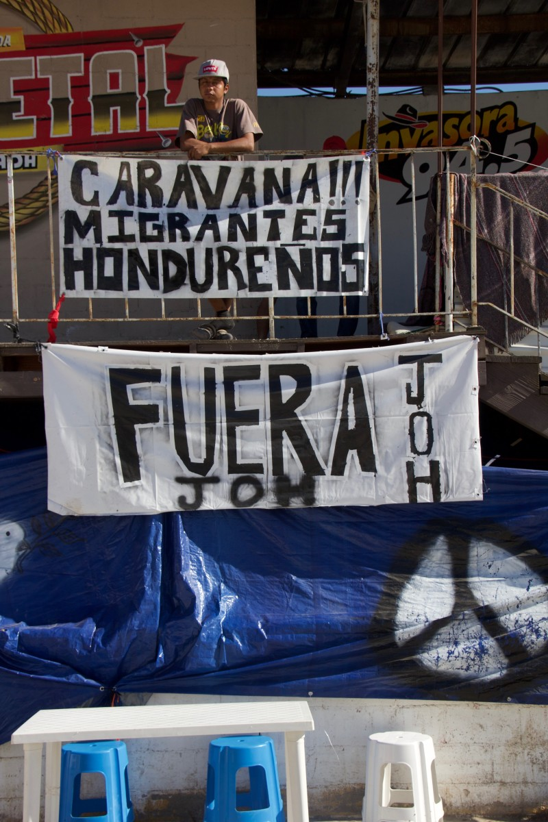 "Inside El Barretal, a banner reads ""Caravan! Honduran Migrants."" The banner below it reads ""Get Out, J.O.H""—the initials of Honduras' controversial president, Juan Orlando Hernández."