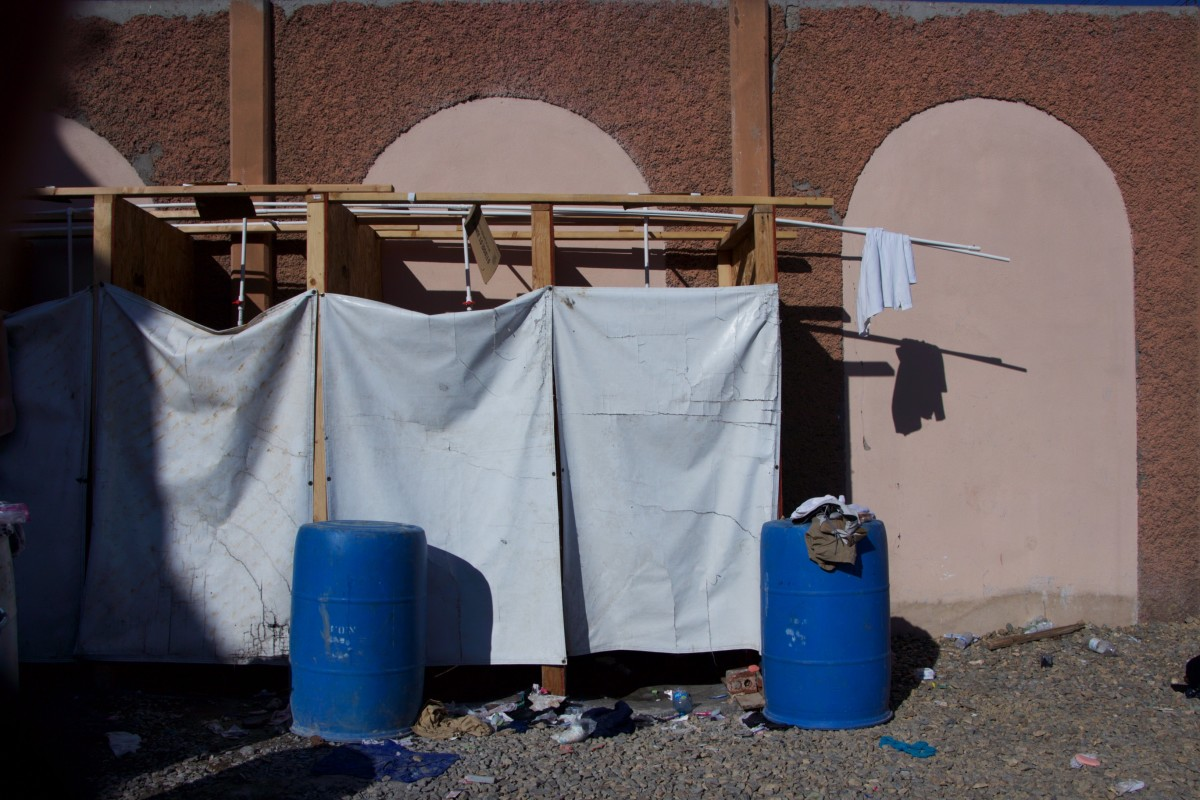Four shower stalls made out of plywood and PVC piping. These showers are only available to children and families in El Barretal. The rest of the camp's residents use sinks to bathe.