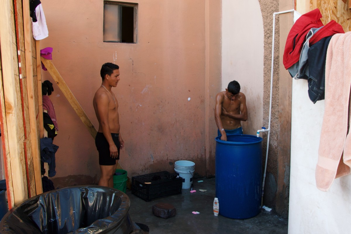 Two migrants wash in the rudimentary bathing area inside the pavilion for children and families.