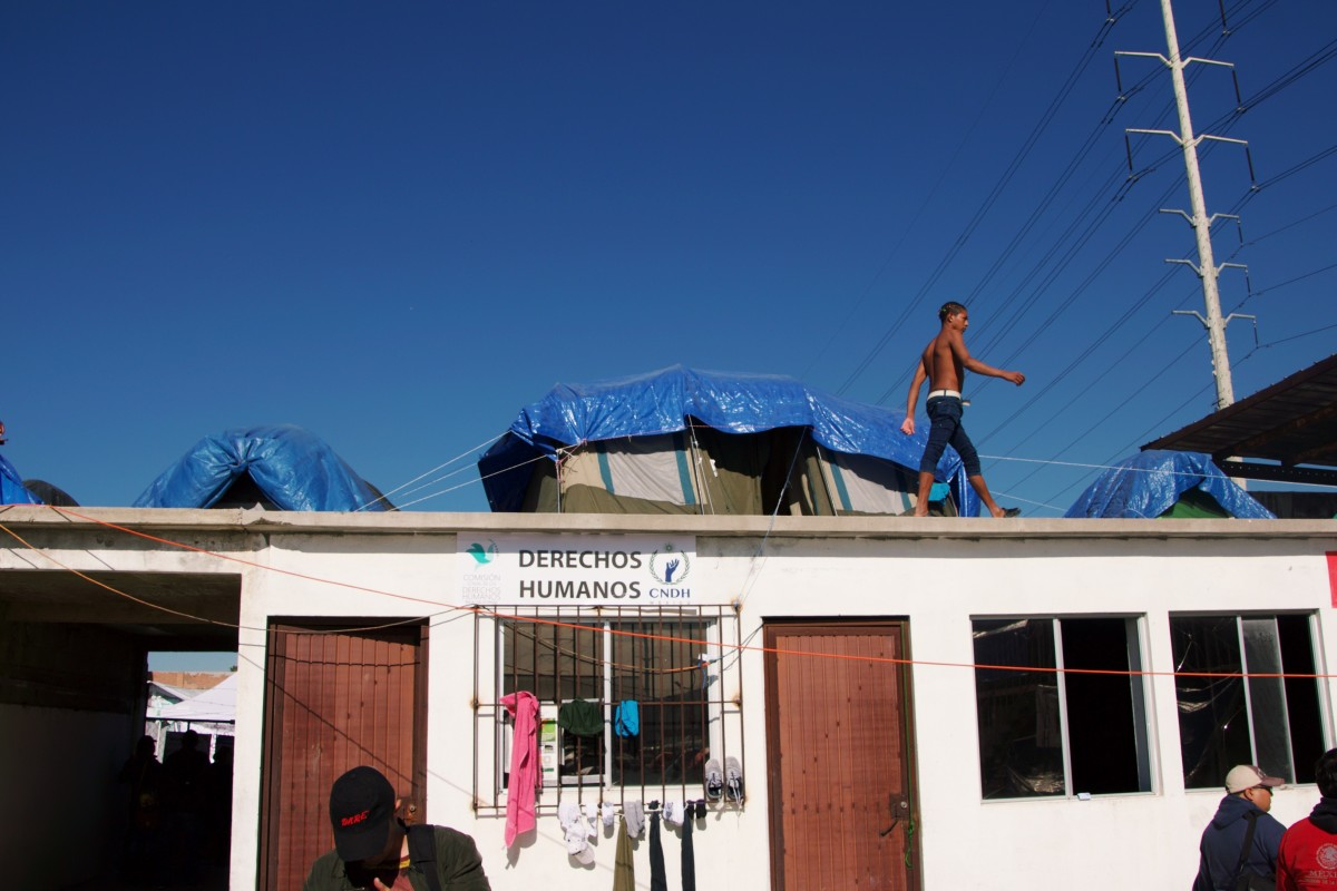 "A migrant from Honduras walks by his family's tent on a roof above a portion of El Barretal, the main shelter for migrants who arrived in two caravans from Central America into Tijuana, Mexico in November. The sign below him reads ""Derechos Humanos"" (Human Rights)."