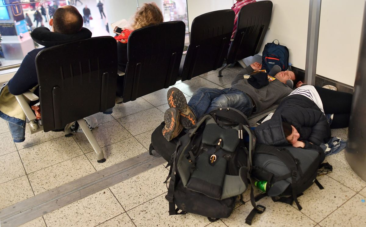 "Passengers lay on the floor with their luggage in the South Terminal building at London Gatwick Airport, south of London, on December 21st, 2018, as flights started to resume following the closing of the airfield. British police on Friday were considering shooting down the drone that has grounded flights and caused chaos at the airport, with passengers set to face a third day of disruption. Police said it was a ""tactical option"" after more than 50 sightings of the device near the airfield since Wednesday night, when the runway was first closed."