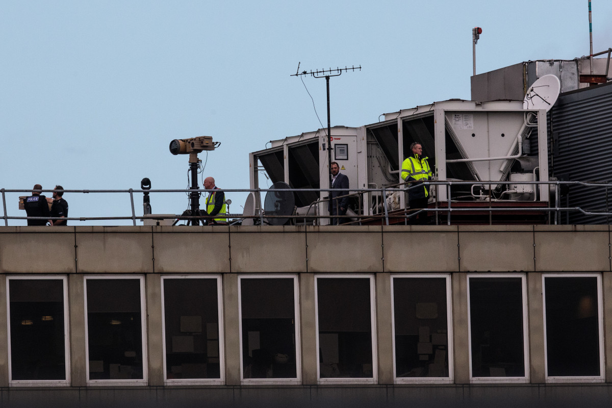 Officials stand near equipment and survey the runway at Gatwick Airport on December 21st, 2018.
