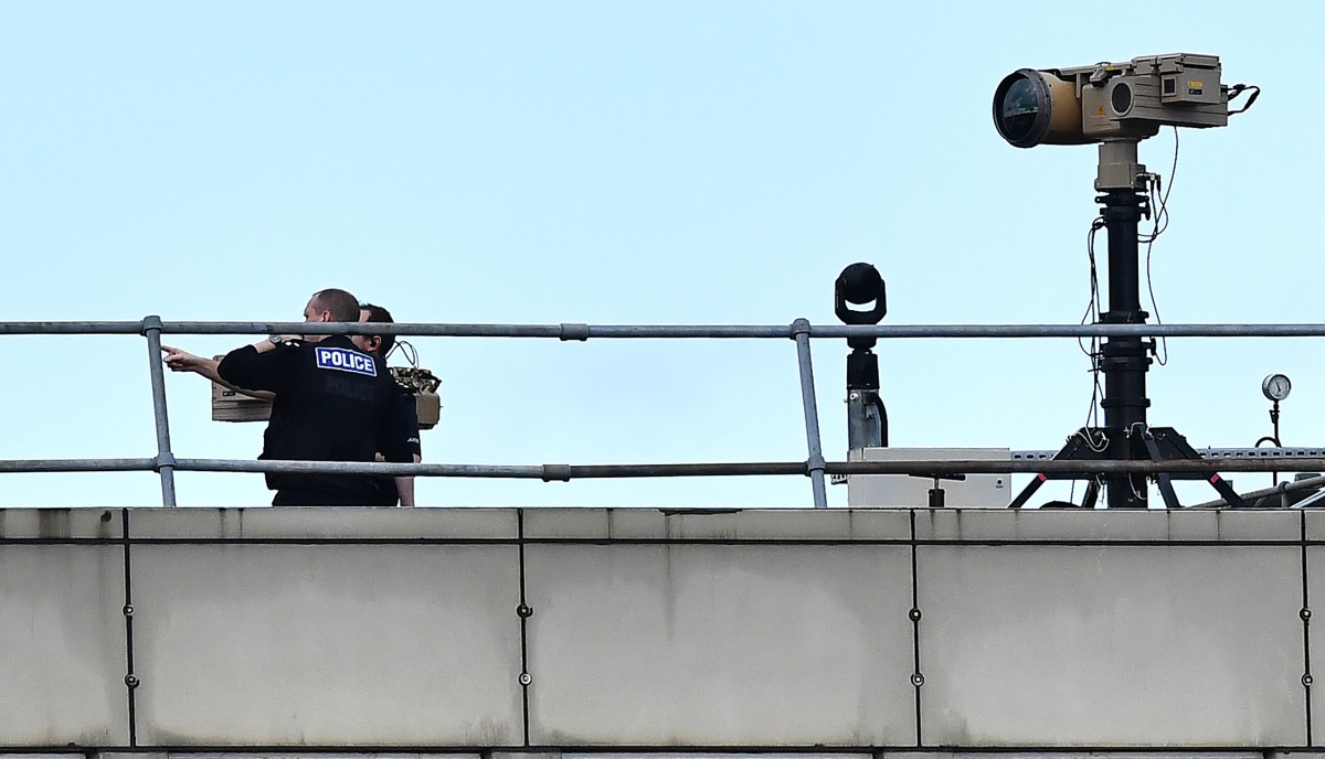 Police officers stand near equipment on the rooftop of a building at Gatwick Airport on December 21st, 2018.