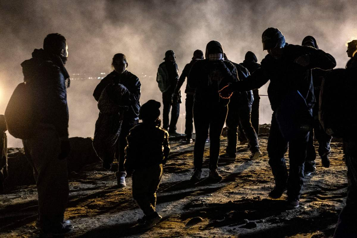 A group of Central American migrants walk away from tear gas thrown by the US border patrol, after they tried to cross from Tijuana to San Diego in the US, as seen from Tijuana, Baja California state, Mexico on January 1, 2019. - Around 100 Central American migrants made a failed attempt on New Year's Eve to cross over from Mexico into the United States. As night fell and people on both sides of the frontier prepared to celebrate New Year's Eve, the migrants tried to cross over but at least two smoke bombs were hurled and they ultimately held back.